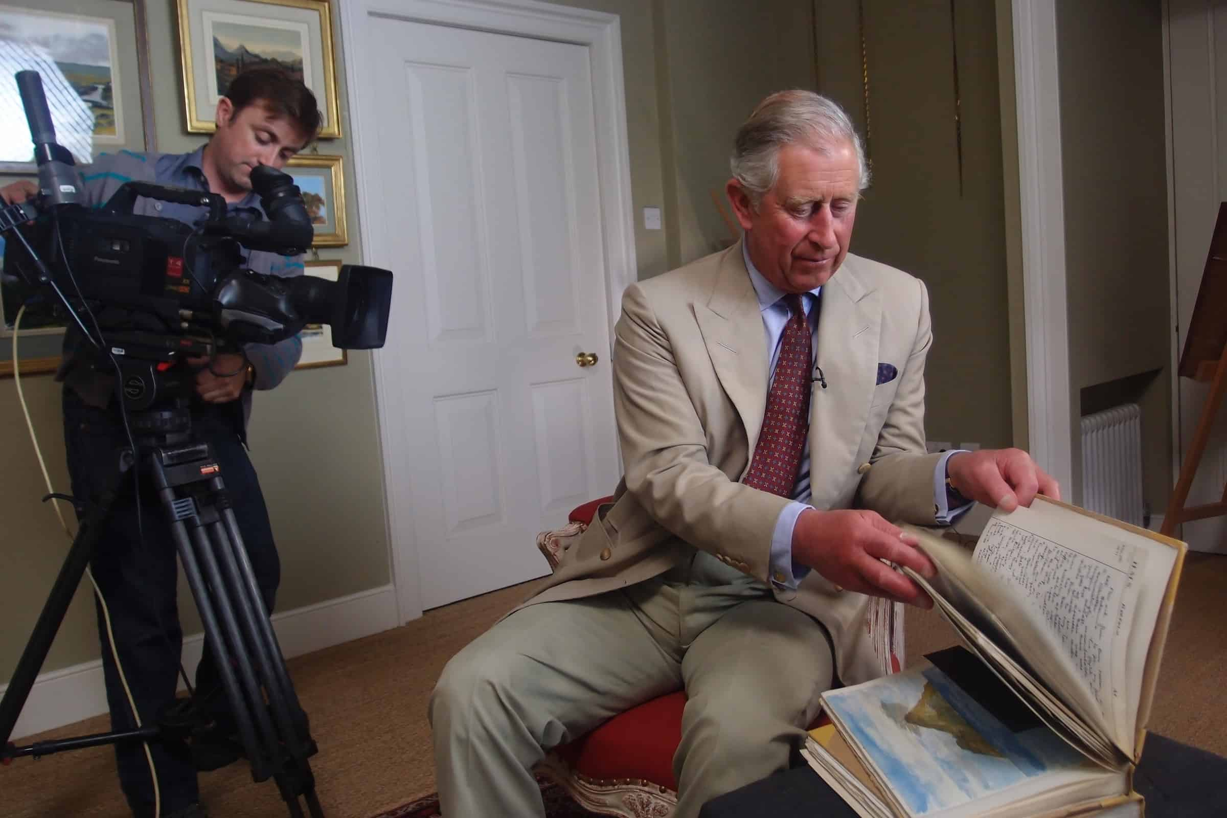 HRH The Prince of Wales looking through his naval notebook during the filming of Royal Paintbox